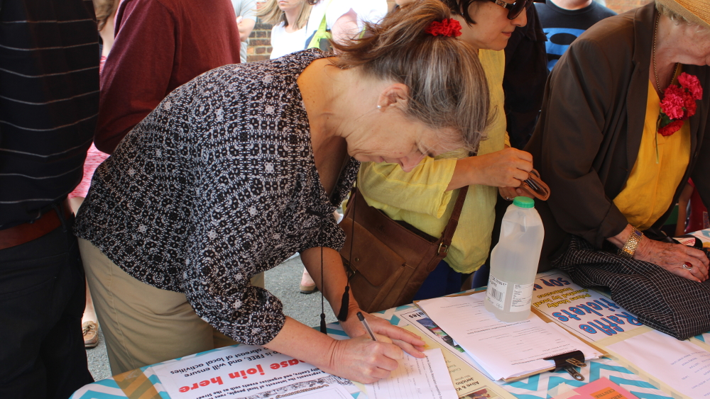 <p>Susan Moser signs up as a member of the Jericho Community Association</p>